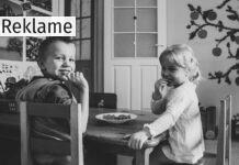En dreng og en pige der sidder ved et bord og spiser